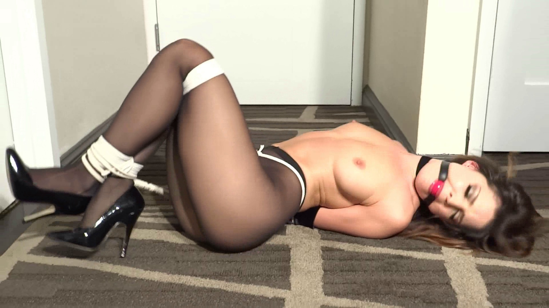 Brooke Thompsen hogtied by the hotel room door