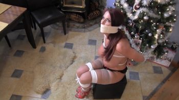 Busty trophy wife left struggling wrapped up and muffled under the Christmas Tree