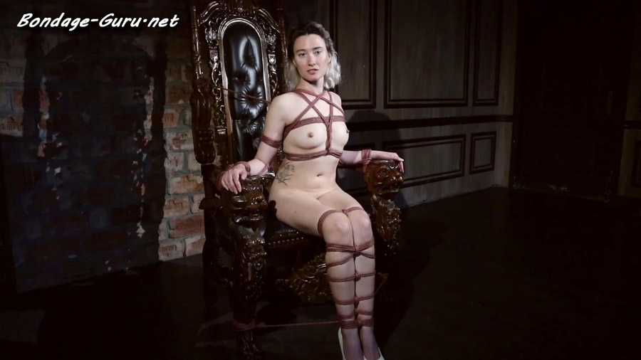 Sofi is tied with ropes to a large wooden throne Version 2 Backstage